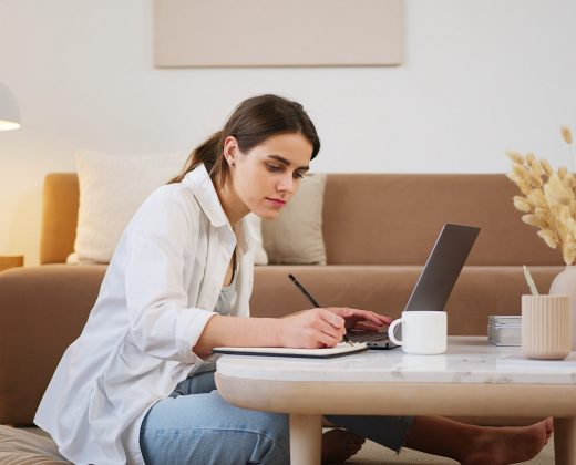 young-woman-using-laptop-and-taking-notes-4492126